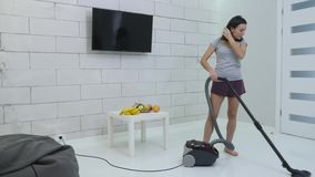 A young girl is cleaning the house using a vacuum cleaner.  stock footage