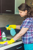 Young girl cleaning sink in the kitchen Royalty Free Stock Photos
