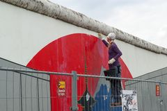 A young girl cleans the Berlin Wall, East Side Gallery, Berlin. stock images