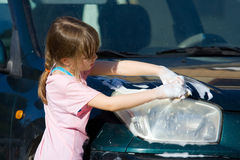 Young Girl Cleans Car Headlight. Young girl cleans car for pocket money, makes game of it. Handwashing car to save water and earn pocket money stock image