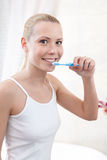 Young girl cleans her teeth Stock Photos