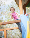 Young girl climbing on childrens playground and waving at camera Stock Photo