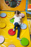Young girl climbing down ramp in soft play centre Stock Photo