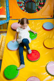 Young girl climbing down ramp in soft play centre Royalty Free Stock Photo