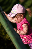 Young girl climbing on fence Stock Photos