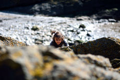 Young girl climbing rocks on the coast Royalty Free Stock Image