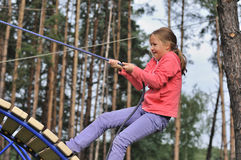 Girl climbing on a rope Stock Photography