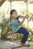 Young Girl Climbing Rope Ladder To Treehouse Royalty Free Stock Image