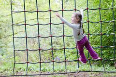 Young girl climbing on rope net frame in outdoor woodland adventure parkground royalty free stock photos