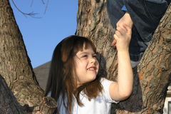 Young girl climbing tree. Closeup of young girl climbing tree with help of other person Stock Photo