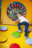 Young girl climbing up ramp into tunnel at soft play centre royalty free stock photo
