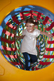 Young girl climbs through netted tunnel in soft play centre Stock Photography