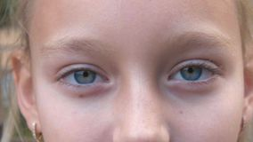 Young girl with closed eyes closeup. Face girl with gray eyes looking in camera. Young girl with closed eyes close up. Face girl with gray eyes looking into stock video footage