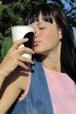 Girl with closed eyes holds a white paper cup stock image