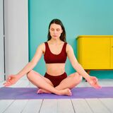Young girl with closed eyes in a sports uniform in a yoga pose sits on a purple rug