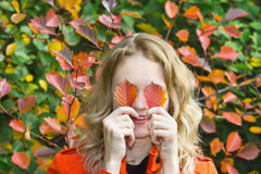 Young girl closed her eyes autumn leaves. Young beautiful blonde girl closed her eyes autumn leaves Royalty Free Stock Photo