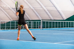 The young girl in a closed tennis court with ball Royalty Free Stock Photo