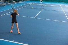 The young girl in a closed tennis court with ball Stock Images