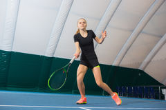 The young girl in a closed tennis court with ball Royalty Free Stock Photography