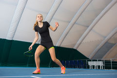 The young girl in a closed tennis court with ball Stock Photography