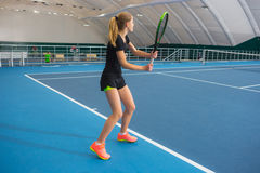 The young girl in a closed tennis court with ball Stock Image