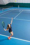 The young girl in a closed tennis court with ball Royalty Free Stock Image