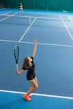The young girl in a closed tennis court with ball Stock Photo