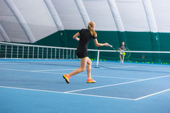 The young girl in a closed tennis court with ball Royalty Free Stock Photos