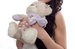 Young girl closeup holds in hands of toy bear. Young girl on white background close-up holds the toy light beige bear Royalty Free Stock Photo