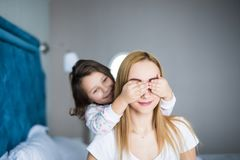 Young girl is closing her mother eyes. Beautiful mother and her little daughter are smiling on bed at home. royalty free stock image