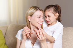 Young girl is closing her mother eyes. Beautiful mother and her little daughter are smiling. Royalty Free Stock Image