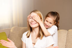 Young girl is closing her mother eyes. Beautiful mother and her little daughter are smiling. Stock Images
