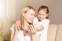 Young girl is closing her mother eyes. Beautiful mother and her little daughter are smiling. People happiness, leisure stock images