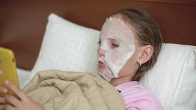 Young girl with cloth cosmetics mask on skin face lying on bad. Teenager girl using smartphone while cosmetics mask in. Home. Problem skin care and treatment stock video footage