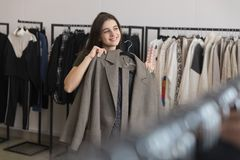 A young girl in a clothing store chooses a coat. royalty free stock photo