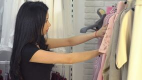 Young girl in clothing store. Shopping concept stock video footage