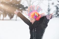 Young girl with clown colorful wig and headphones on snow day. royalty free stock photography