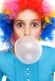 Young girl with clown wig and bubble gum. Isolated on white Royalty Free Stock Photography