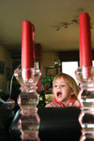 Young girl clowning. Between two candles royalty free stock photos