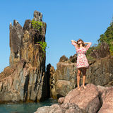 Young  girl on a coastal rocks the sea. Stock Photography