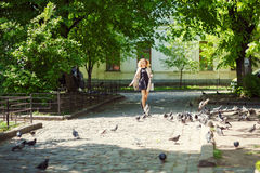 A young girl in a coat and carrying a bag in her hands is running along the street of the old city, dispersing pigeons.  stock photography