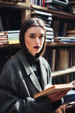 Young girl in coat holding book in an old library Stock Photo