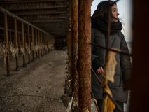 Young girl in a coat stands near metal rusty structures near the sea coast.  stock photography