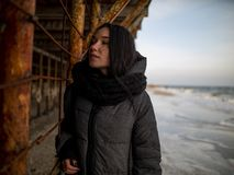 Young girl in a coat stands near metal rusty structures near the sea coast.  royalty free stock photo