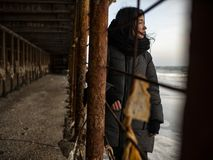Young girl in a coat stands near metal rusty structures near the sea coast.  royalty free stock images