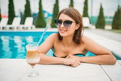 Young girl with cocktail near the swimming pool Royalty Free Stock Photos