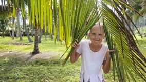 Young girl and coconut branch with leaves stock video