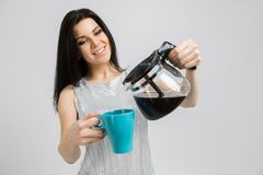Young girl with a coffee pot and a mug stands isolated on a light background royalty free stock images