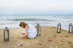 Young girl collecting flower petals on the beach Stock Photo