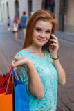 Young girl with colorful shopping bags calling her friend. Royalty Free Stock Image
